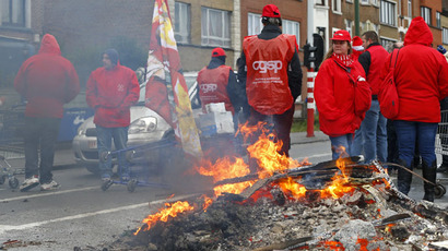 Workers and members of trade unions block a road outside the entrance to an Audi plant in Brussels, December 8, 2014. A strike in parts of Belgium on Monday disrupted rail services and Belguim's national airport as trade unions and workers voice their anger over austerity measures announced by the country's new government. (Reuters/Yves Herman)