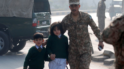 A soldier escorts schoolchildren after they were rescued from from the Army Public School that is under attack by Taliban gunmen in Peshawar, December 16, 2014. (Reuters/Khuram Parvez)