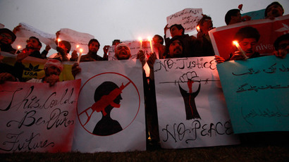 People hold candles and signs to condemn the Taliban attack on the Army Public School in Peshawar, during a rally in Lahore December 19, 2014. (Reuters / Mohsin Raza)