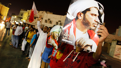 Protesters, holding placards with an image of Al Wefaq Secretary-General Sheikh Ali Salman, shout anti-government slogans as they gather outside Salman's home, in the village of Bilad Al Qadeem, south of Manama, December 28, 2014 (Reuters / Hamad I Mohammed)