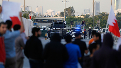 Riot police gather in front of protesters demonstrating for Al Wefaq Secretary-General Sheikh Ali Salman in the village of Bilad Al Qadeem, south of Manama, December 29, 2014 (Reuters / Hamad I Mohammed)