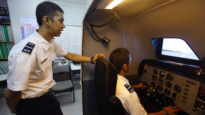 A student watches his colleague practice on a flight simulator at the Deraya Flight School in Jakarta, Indonesia (Reuters / Beawiharta)