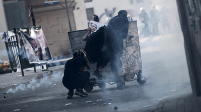 Bahraini protestors take cover behind a garbage container during clashes with riot police following a protest against the arrest of the head of the banned Shiite opposition movement Al-Wefaq, Sheikh Ali Salmanon January 1, 2015 in Bilad al-Qadeem, a suburb of Manama. (AFP Photo / Mohammed Al-Shaikh)