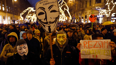 "People wear Guy Fawkes masks and hold a placard reading ""Regime"" during an anti-government protest called by civil groups in Budapest January 2, 2015 (Reuters / Laszlo Balogh)"