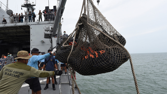 Personnel on the Indonesian Navy vessel KRI Banda Aceh lift body bags containing dead bodies recovered during a search operation for passengers of AirAsia flight QZ8501, at sea January 3, 2015 (Reuters / Adek Berry)