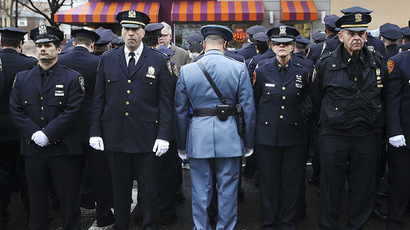 Law enforcement officers stand, with some turning their backs, as New York City Mayor Bill de Blasio speaks on a monitor outside the funeral for NYPD officer Wenjian Liu in the Brooklyn borough of New York January 4, 2015. (Reuters/Shannon Stapleton)