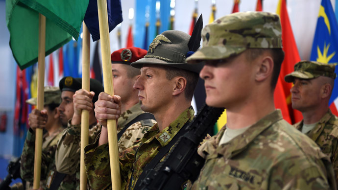 NATO-led International Security Assistance Force (ISAF) soldiers carry flags during a ceremony marking the end of ISAF's combat mission in Afghanistan at ISAF headquarters in Kabul on December 28, 2014. (AFP Photo/Shah Marai)