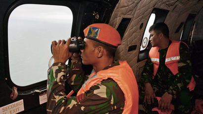 A crewmember of an Indonesian Air Force Super Puma helicopter of the 6th Air Squadron uses binoculars to scan the horizon during search operations for victims of AirAsia Flight QZ 8501 over the Java Sea on January 1, 2015. (AFP Photo)