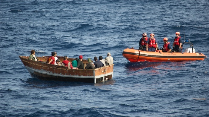 A US Coast Guard cutter approaches a rustic vessel with 12 Cuban migrants aboard. They were later repatriated to Bahia de Cabañas, Cuba, Jan. 5, 2015. (USCG)