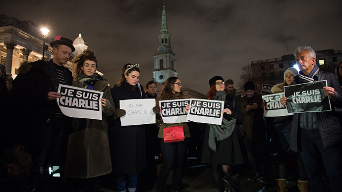 "People hold posters as they gather in Trafalgar Square in central London to show their respect for the twelve people killed in Paris today in a terrorist attack at the headquarters of satirical publication ""Charlie Hebdo"" on January 7, 2015 (AFP Photo / Leon Neal)"