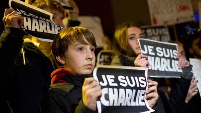 "People hold up ""Je Suis Charlie"" placards at a vigil outside The French Institute in London on January 9, 2015.(AFP Photo / Justin Tallis)"