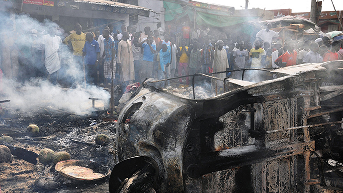 ARCHIVE PHOTO: People gather to look at a burnt vehicle following a bomb explosion that rocked the busiest roundabout near the crowded Monday Market in Maiduguri, Borno State, on July 1, 2014 (AFP Photo / Stringer)