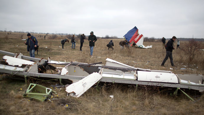 Journalists look at parts of the Malaysia Airlines plane Flight MH17 as Dutch investigators (unseen) arrive at the crash site near the Grabove village in eastern Ukraine on November 11, 2014, hoping to recover debris from the Malaysia Airlines plane which crashed in July, killing 298 people, in remote rebel-held territory east of Donetsk. (AFP Photo)