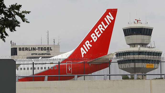 An Air-Berlin aircraft passes along the air traffic control tower and terminal building at Berlin's Tegel airport. (Reuters/Fabrizio Bensch)