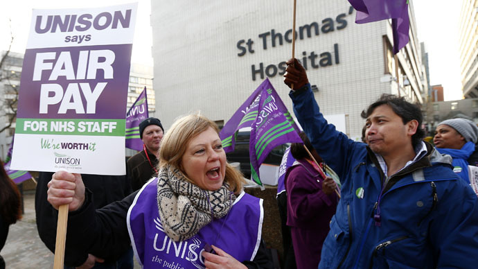 NHS workers hold placards as they stand on a picket line outside St. Thomas' Hospital in central London November 24, 2014. (Reuters/Andrew Winning)