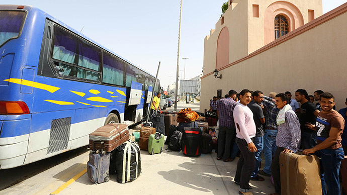 Egyptian workers gather with their belongings next to a bus in the Libyan capital Tripoli. (AFP Photo)
