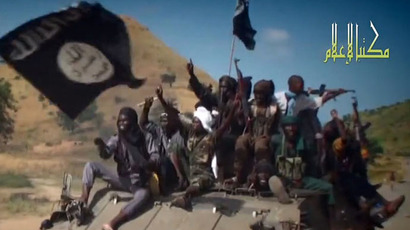 A screengrab taken on November 9, 2014 from a new Boko Haram video released by the Nigerian Islamist extremist group Boko Haram and obtained by AFP shows Boko Haram fighters parading on a tank in an unidentified town. (AFP Photo)