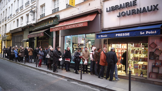 People wait outside a newsagents in Paris on January 14, 2015 as the latest edition of French satirical magazine Charlie Hebdo goes on sale. (AFP Photo / Martin Bureau)