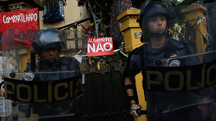 "Riot police stand in front of a sign that reads, ""No to fare hikes"" hung on the gate of a house during a protest against fare hikes for city buses, subways and trains in Sao Paulo January 16, 2015 (Reuters / Nacho Doce)"