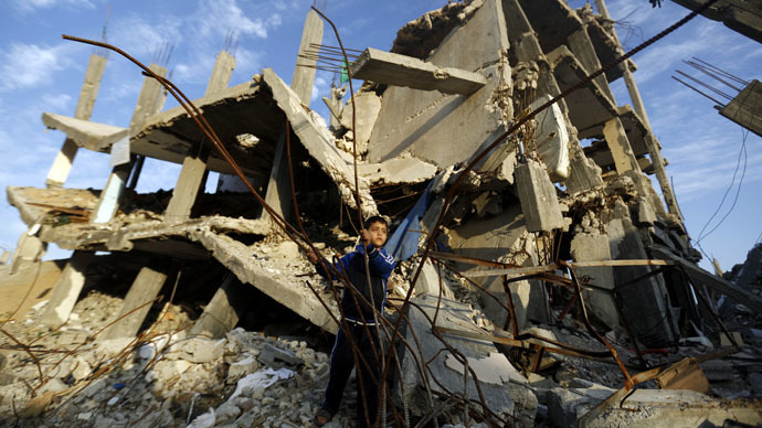 A Palestinian boy plays in the rubble of a house destroyed during the 50 days of conflict between Israel and Hamas last summer, in the Shejaiya neighborhood of Gaza City, on Decembre 11, 2014. (AFP Photo/Mohammed Abed)