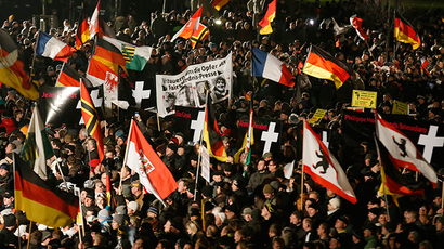 Supporters of anti-immigration movement Patriotic Europeans Against the Islamization of the West (PEGIDA) hold flags during a demonstration in Dresden January 12, 2015 (Reuters / Fabrizio Bensch)