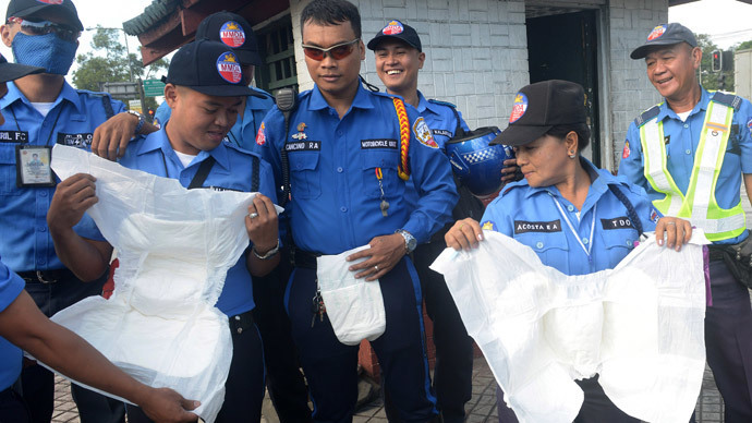 Traffic enforcers of the Metro Manila Development Authority display adult diapers in Manila on January 8, 2015, that they were issued, to ensure they can stay at their posts when Pope Francis visits the Philippines between January 15-19. (AFP Photo / Jay Directo)