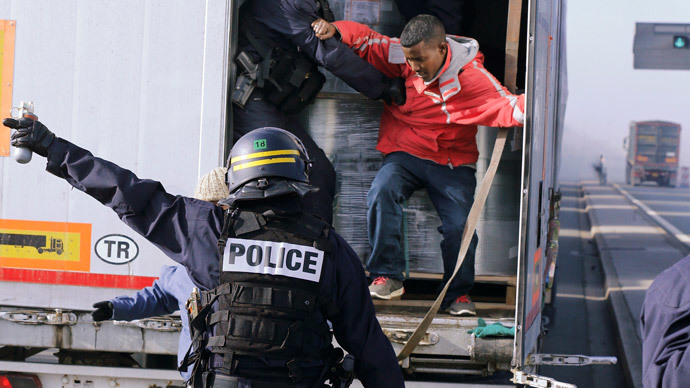 French riot policemen force out migrants who were hidden in a lorry which makes its way to the ferry terminal in Calais October 22, 2014.(Reuters / Pascal Rossignol)