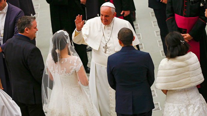Pope Francis waves to newlywed couples during his Wednesday general audience in Paul VI hall at the Vatican January 21, 2015. (Reuters / Tony Gentile)