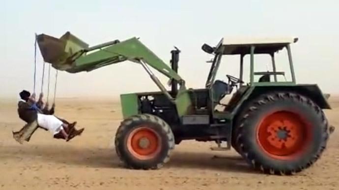 Having fun in Saudi desert: Daredevils swinging from reversing tractor (VIDEO)