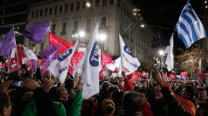 Syriza supporters wave a Greek national flag and other flags after opposition leader and head of radical leftist Syriza party Alexis Tsipras gave a speech during a campaign rally in central Athens, January 22, 2015 (Reuters / Yannis Behrakis)
