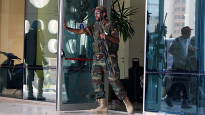 ARCHIVE PHOTO: A rebel fighter opens a door of the Corinthia Hotel after gunfight with forces loyal to Muammar Gaddafi in Tripoli August 25, 2011 (Reuters / Louafi Larbi)