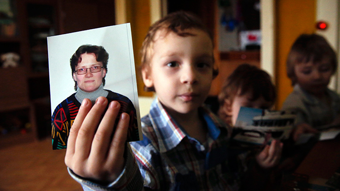 Artur, son of Russian activist Svetlana Davydova and her husband Anatoly Gorlov, holds up a photo of his mother to the camera, at their home in Vyazma, January 30, 2015 (Reuters / Maxim Zmeyev)