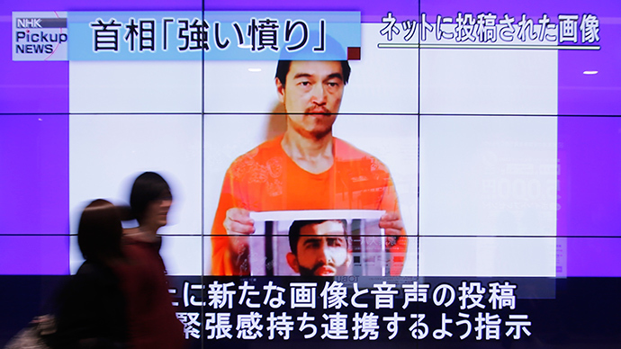 People walk past television screens displaying a news program, about an Islamic State video showing Japanese captive Kenji Goto, on a street in Tokyo  (Reuters / Yuya Shino)