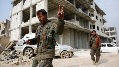 A fighter of the Kurdish People's Protection Units (YPG) flashes a V-sign as he patrols in the streets in the northern Syrian town of Kobani January 28, 2015.(Reuters / Osman Orsal)
