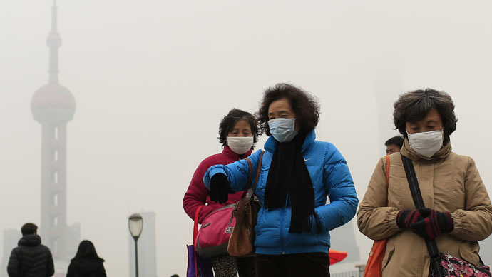 Woman wear face masks on the Bund in front of the Oriental Pearl TV Tower during a hazy day in downtown Shanghai January 26, 2015. (Reuters/Aly Song)