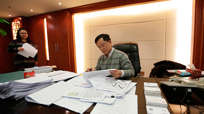 Guan Jianzhong, chairman of Beijing-based Dagong Global Credit Rating Co, works at his office in Beijing (Reuters / Jason Lee)