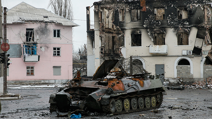 An armoured vehicle and a building, destroyed during battles between the armed forces of the self-proclaimed Donetsk People's Republic and the Ukrainian armed forces, are seen in Uglegorsk, Donetsk region, February 4, 2015 (Reuters / Maxim Shemetov)