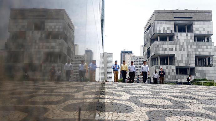 People walk next to the Petrobras headquarters (R) in Rio de Janeiro February 4, 2015 (Reuters / Ricardo Moraes)