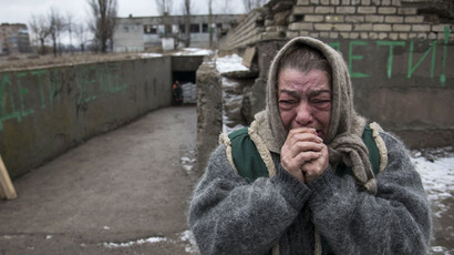 An elderly woman reacts as her acquaintances board a bus to flee due to a military conflict in Debaltseve, February 4, 2015. (Reuters/Sergey Polezhaka)
