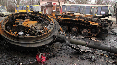 Burnt military machinery in Uglegorsk. Background: a DPR bus column heading to Debaltsevo for evacuation of local residents from the combat zone. (RIA Novosti)