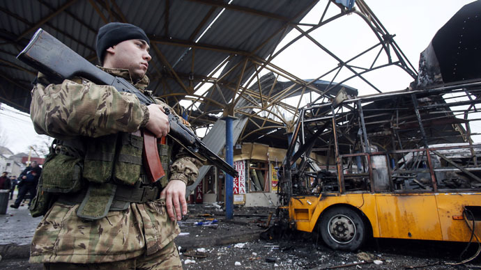 A member of the armed forces of the self-proclaimed Donetsk People's Republic stands guard near a destroyed vehicle at a bus station after shelling in Donetsk, February 11, 2015. (Reuters/Maxim Shemetov)