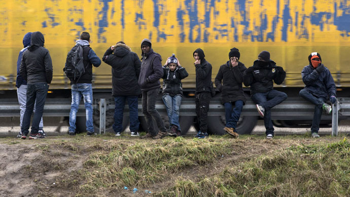 Migrants wait to jump on lorries at a nearby gas station on the highway in Calais (Reuters/Philippe Wojazer)