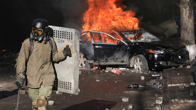 A protester holds a makeshft shield in front of a burning car during clashes with police in Kiev February 18, 2014. (Reuters / Konstantin Chernichkin)