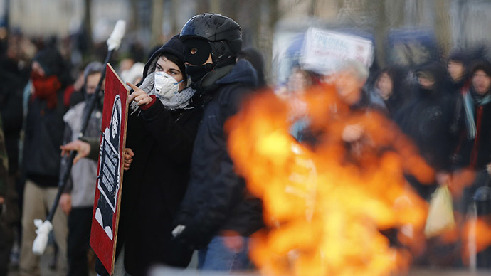 Masked protesters look on during clashes with French riot police at a demonstration to mark the one-year anniversary of a protest march in 2014 which ended in violence, in Nantes February 21, 2015. (Reuters/Stephane Mahe)