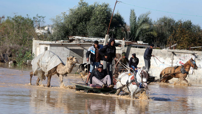 Palestinians ride horse carts as they evacuate their animals in the village of Al-Moghraga after it was flooded by rain water, near central Gaza Strip February 22, 2015. (Reuters / Ibraheem Abu Mustafa )