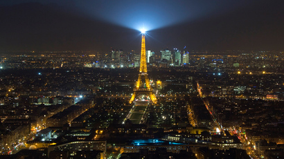 A view shows the illuminated Eiffel Tower and La Defense business district (background) in Paris February 24, 2015 (Reuters / Gonzalo Fuentes)