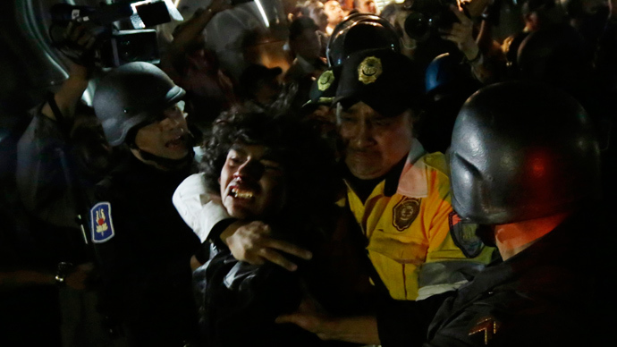 A protester (C) is detained by riot police after a protest march to demand justice for the 43 missing students of the Ayotzinapa Teacher Training College, at Zocalo Square in Mexico City February 26, 2015 (Reuters / Henry Romero)