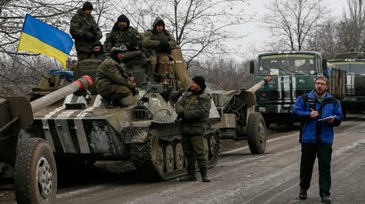 A member of Special Monitoring Mission of the Organization for Security and Cooperation (OSCE) to Ukraine walks along a convoy of Ukrainian armed forces in Paraskoviyvka, eastern Ukraine, February 26, 2015 (Reuters / Gleb Garanich)