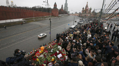 People visit the site where Boris Nemtsov was recently murdered, with St. Basil's Cathedral and the Kremlin walls seen in the background, February 28, 2015. (Reuters/Maxim Zmeyev)