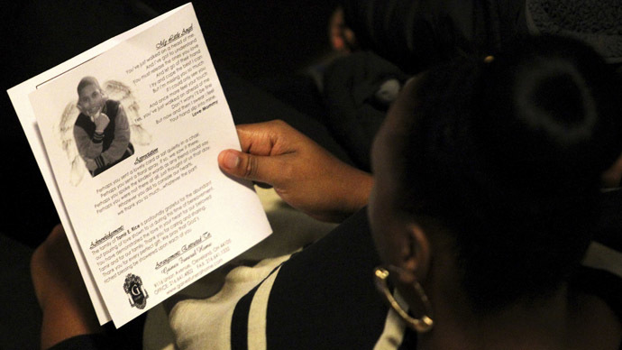 A mourner reads the obituary from the program during the funeral service for Tamir Rice in Cleveland, Ohio. (Reuters/Aaron Josefczyk)